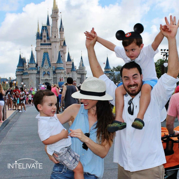 a family in front of the castle at disney world